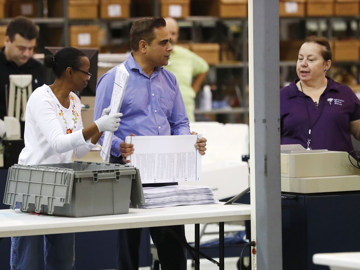 The Latest: Palm Beach machines overheat, miss recount votes