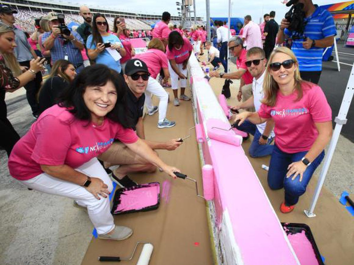 Jimmie Johnson and group of breast cancer survivors paint Charlotte Motor Speedway pit wall pink